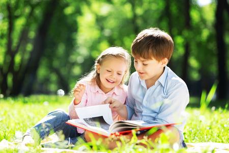 姉と弟は本を読んで公園で 写真素材