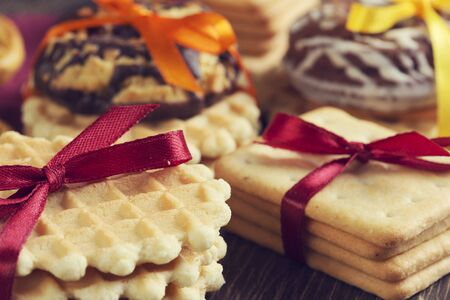 Stack of delisious cookies and biscuits folded with ribbon photo