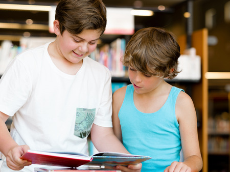 Two boys in library with books photo