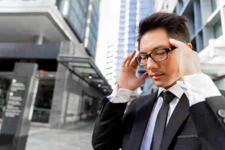 concentrate on: Businessman standing in street and trying to concentrate Stock Photo