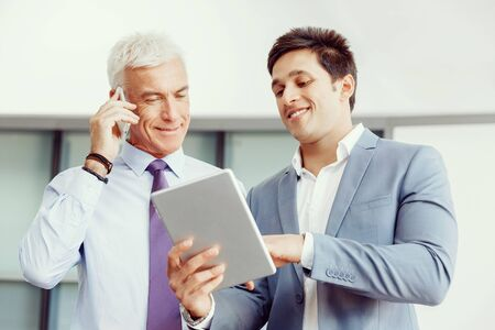 Two businessman in office with devices photo