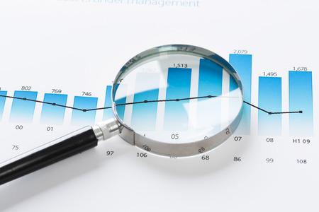 Magnifing verre et documents avec des données d'analyse couché sur la table