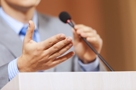 public speaker: Businessman standing on stage and reporting for audience Stock Photo
