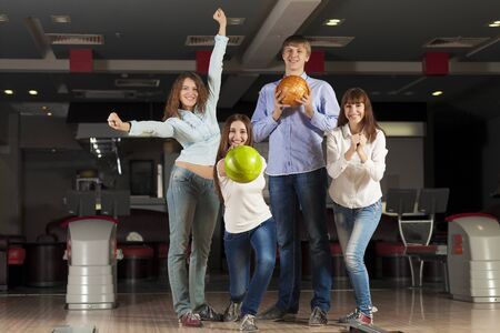 Group of four young smiling people playing bowling photo