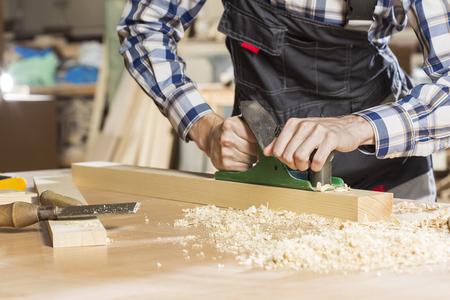 carpintero: Close up de manos de carpintero trabaja con el plano en su estudio
