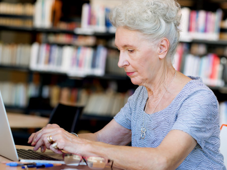 Elderly lady working with laptop Stock Photo