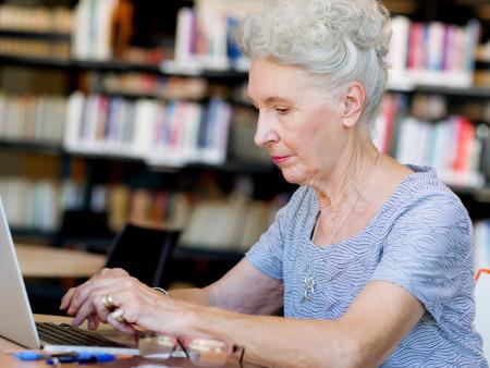 Oudere dame met een laptop werkt