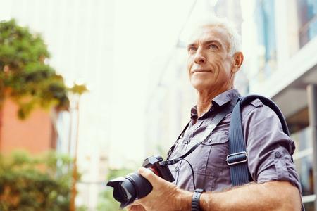 hombre viejo: Hombre mayor con la c�mara en la ciudad