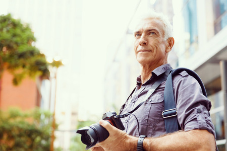 old picture: Senior man with camera in city Stock Photo
