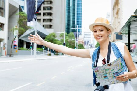 hailing: Female tourist calling for a taxi in the city