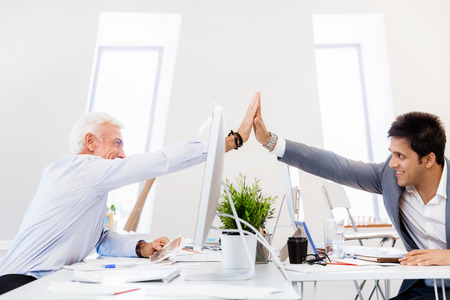 Businessmen in office cheering at their success