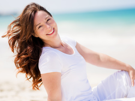 mature female: Woman in white clothes on the beach on sunny day
