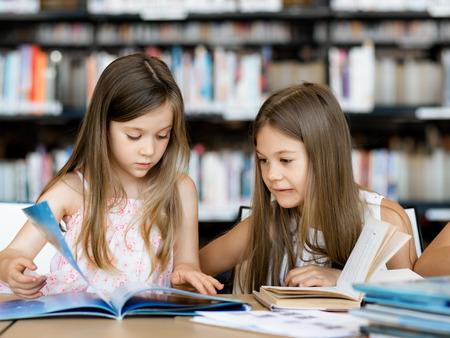 biblioteca: Las niñas la lectura de libros en la biblioteca Foto de archivo