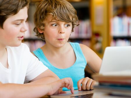 Two boys in library with notebook photo