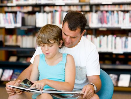 family portrait: Father with son in library with books Stock Photo