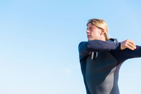 wetsuit: A young surfer putting on his wetsuit on the beach