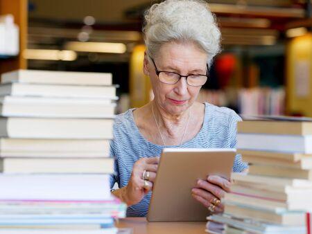 profesor: Señora mayor que trabaja con la tableta