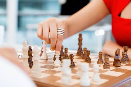 chess: Mujer de negocios que se sienta delante de ajedrez y la planificación