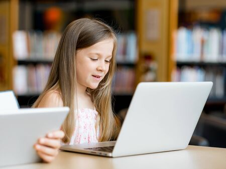 e pretty: Little girls with a laptop in library