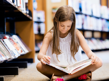Little girl sitting on the floor and reading books in library Zdjęcie Seryjne