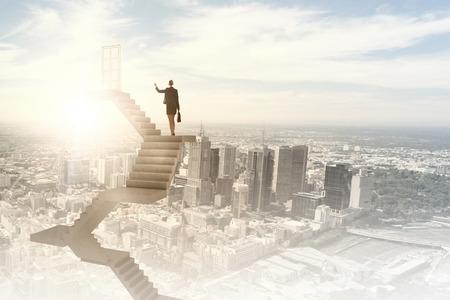 Businesswoman walking up staircase to door in sky 写真素材