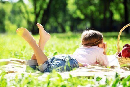 Child lying on blanket having picnic in summer park