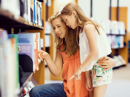 holding mother's hand: Mother and daughter picking a book in public library