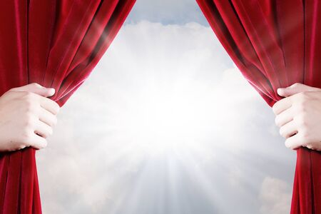 Close up of hand opening red curtain. Place for text Imagens
