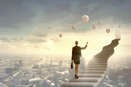 Businesswoman walking up staircase to door in sky 스톡 콘텐츠