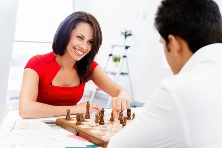 jugando ajedrez: Empresaria jugando al ajedrez en la oficina Foto de archivo