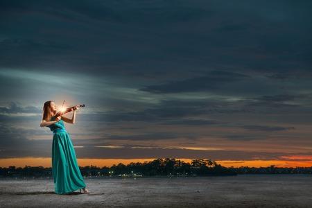 Virtuoso violin female player in green dress