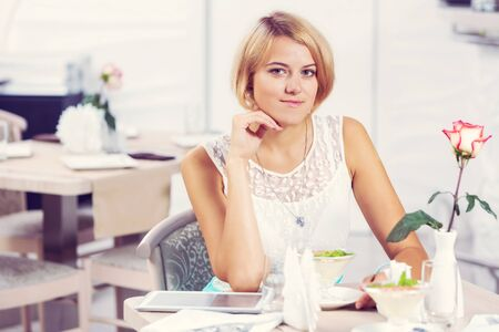 blond haired: Young pretty blond haired woman sitting in cafe