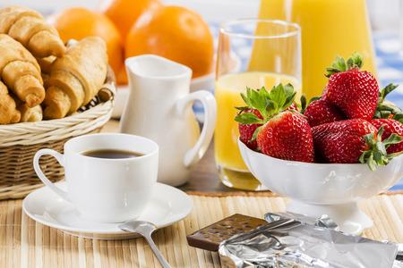 Ontbijt met assortiment van broodjes, koffie en verse aardbeien