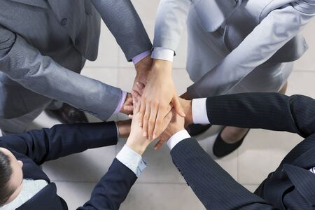 coalition: Close up of business peoples hands on top of each other