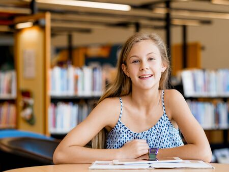 intelligently: A teenage girl with a book in library Stock Photo