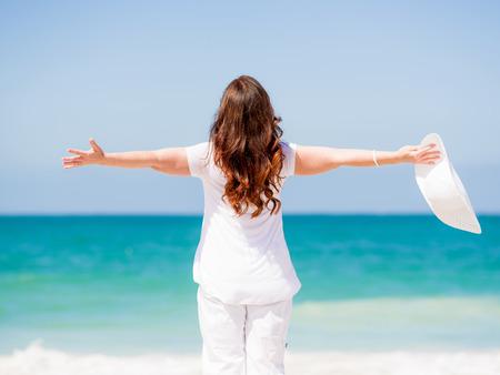 dia soleado: Mujer en la ropa blanca en la playa en un día soleado
