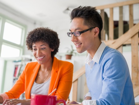 couple talking: Two desingers working on a project together in office Stock Photo
