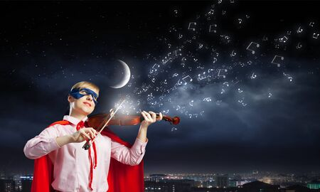 virtuoso: Young woman in super hero costume playing violin