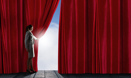 theatre performance: Young woman in business suit opening color curtain of stage