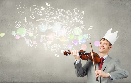 powerful creativity: Young handsome businessman wearing white paper crown and playing violin