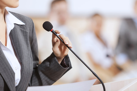 public speaker: Businesswoman standing on stage and reporting for audience Stock Photo
