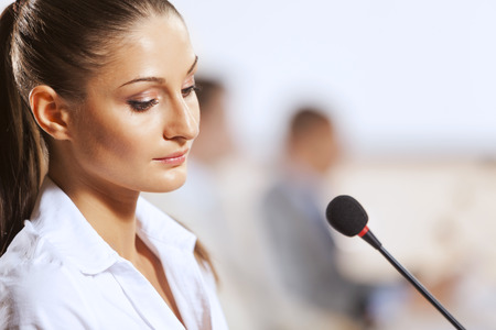 public: Businesswoman standing on stage and reporting for audience Stock Photo