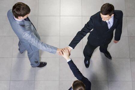 la union hace la fuerza: Close up de manos de la gente de negocios en la parte superior de uno al otro