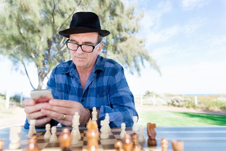 age 60: Portrait of an old man with his mobile phone outdoors Stock Photo