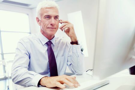 Businessman on the phone sitting at the computer in his office photo
