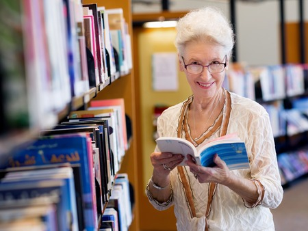Elderly lady standing next to book shelves in library photo