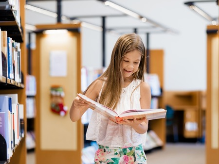 intelligently: Little girl standing and reading books in library Stock Photo