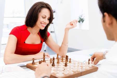 firmeza: Empresaria jugando al ajedrez en la oficina Foto de archivo
