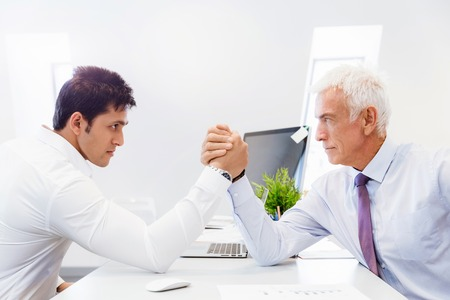 Two businessmen competing arm wrestling in office Stock Photo