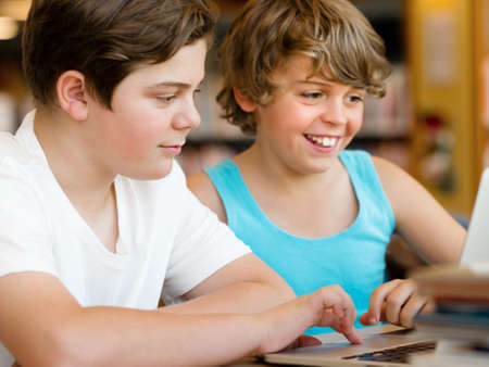Two boys in library with notebook Stock Photo